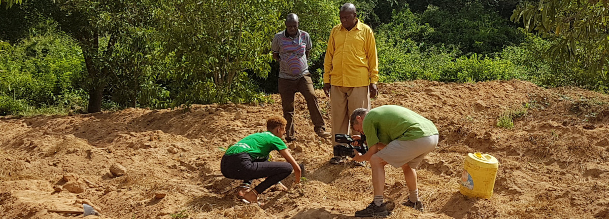 Documentary maker, Tim Tyson Short, filming delegate of Clear the Air: reforest Kenya 2019 conference, Mary Jones, planting a tree to offset her CO2