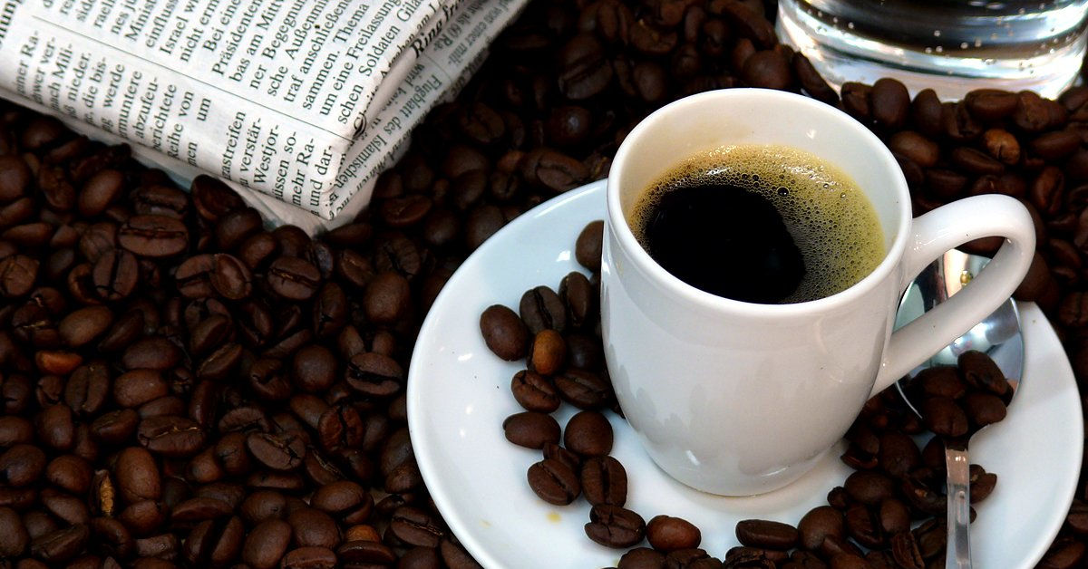 Coffee beans, newspaper and a cup of coffee