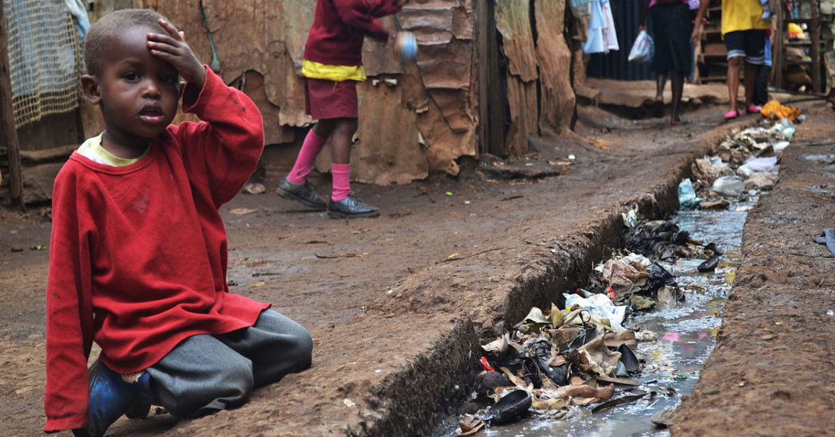 A young boy sits over an open sewer in Kibera, Nairobi