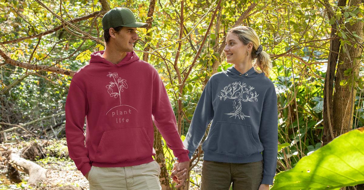 A couple wearing TWFO hoodies in a wood