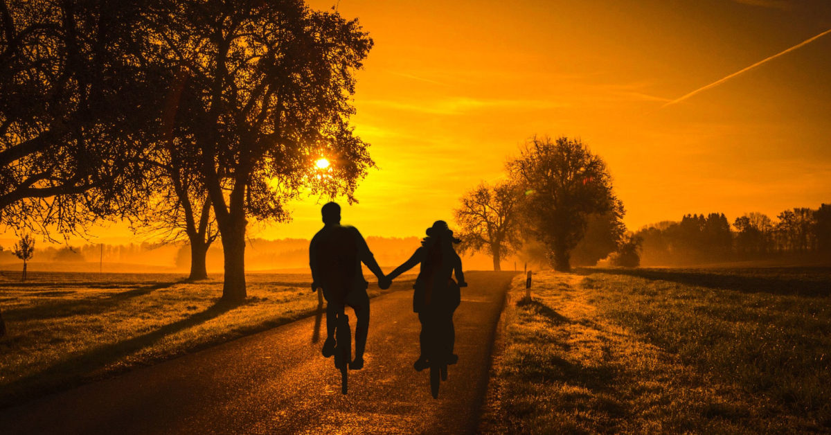 Two people riding bicycles into the sunset in the countryside