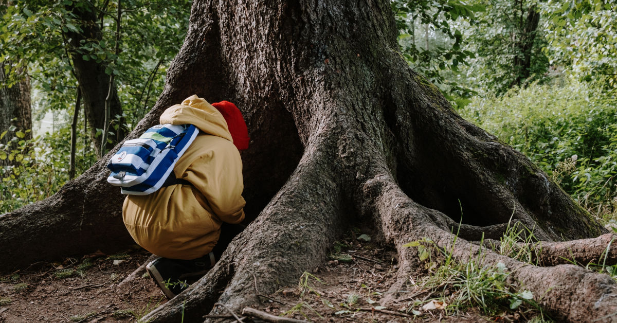 Person in brown jacket and blue denim jeans sitting on brown tree trunk by cottonbro on Pexels