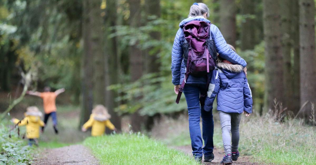 Woman with blue denim jeans and black jacket walking with child by Juliane Liebermann on Unsplash