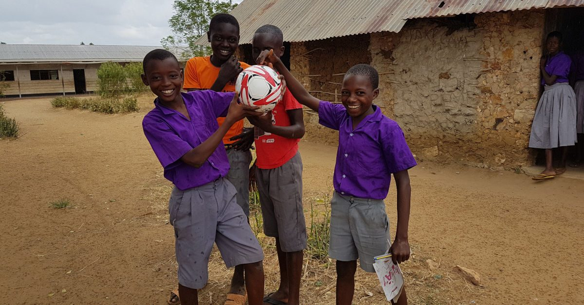 Four Kenyan schoolboys with a football and a girl looking on