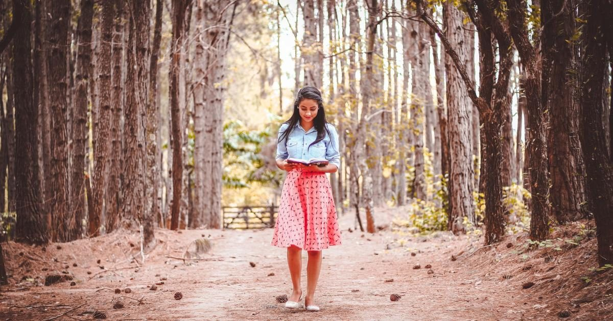a woman reading in the forest